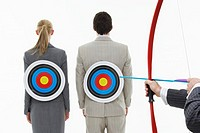 Two business people with targets on backs while man aims bow and arrow close_up of hands against white background