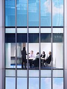 Group of business people at meeting in office view from building exterior (thumbnail)