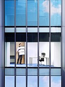 Office worker carrying boxes in office view from building exterior