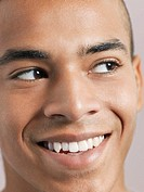 Young man looking aside and smiling close_up of face