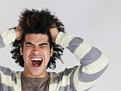 Young man with head in hands screaming