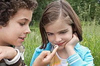 Brother and sister 7-9 examining caterpillar in field (thumbnail)