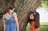 Two girls 7_9 playing hide and seek by tree