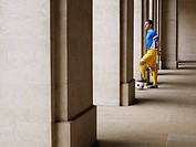 Soccer player holding foot on ball standing in portico