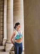 Female athlete wearing gold medal standing in portico