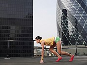 Woman crouching in starting position on downtown rooftop side view London England