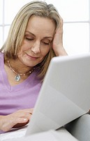 Mid_adult woman using laptop