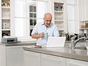 Middle_aged man in kitchen using laptop and holding coffee cup