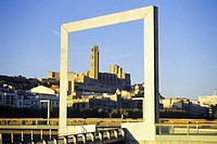 Old cathedral framed by new design metal element in Plaça Blas Infante by Segre river, between Pont Vell and Pont de la Universitat, Lleida. Catalonia...
