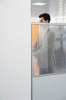 Office worker standing behind cubicle wall