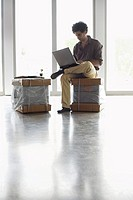 Young man using laptop on packages in empty office