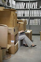 Woman using laptop sitting on floor between boxes in storage room low section
