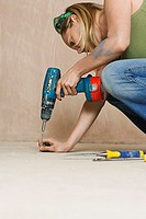 Woman drilling floor close_up