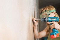 Woman wearing protective goggles drilling wall close_up