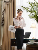 Business woman holding document standing in home office (thumbnail)