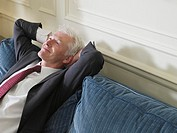 Business man leaning back on sofa elevated view