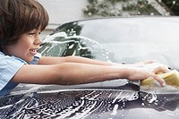 Young boy 7_9 washing car with sponge side view