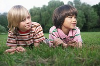 Portrait of two boys 7_9 lying in meadow looking away