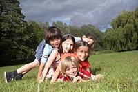 Portrait of five children 7_9 lying on top of each other in meadow