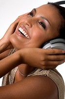 Portrait of a young smiling woman, listening to music with headphones