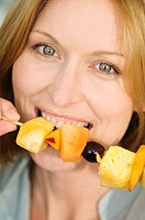 Portrait of a woman eating fruits skewer