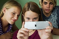 2 teenage girls and boy using camera phone