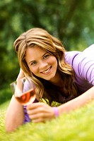 Young smiling woman lying on grass, glass of wine