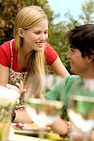 Young couple talking at garden table, outdoors