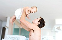 Father and baby playing, man lifting his son, indoors