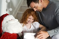 Father and ldaughter opening Christmas presents, indoors (thumbnail)