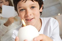 Portrait of a little boy holding a candle, sister in background, indoors