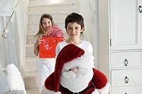 Christmas day, little boy holding a cuddly toy Santa Claus, looking at the camera, sister with present in background, indoors