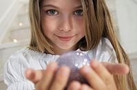 Portrait of a little girl posing for the camera, holding a Christmas ball, indoors