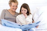 Senior woman and little girl in bed, looking at photograph album
