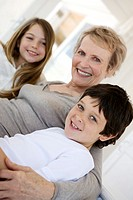 Senior woman and two children smiling for the camera, indoors (thumbnail)