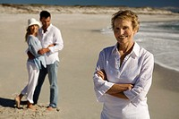 Couple embracing and senior woman on the beach