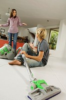 Mother and son in living room, vacuum cleaner, indoors