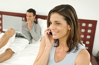Couple in bedroom, woman phoning, indoors