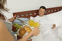 Woman bringing breakfast to man lying on bed, indoors
