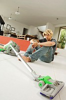 Teenager sitting on floor in living room, vacum cleaner, indoors