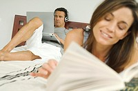 Couple on bed, woman reading, man using laptop, indoors