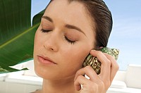 Portrait of a young woman holding a shell against her ear, outdoors (thumbnail)