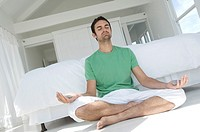 Young man in yoga attitude, indoors
