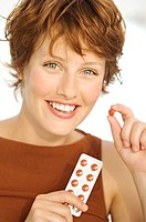 Portrait of a young smiling woman holding pills