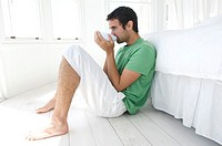 Young man drinking coffee, leaning against bed