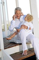 Senior man using mobile phone, with little boy