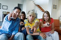 Parents and 2 teens using remote-controls