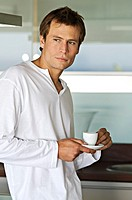 Young thinking man in kitchen, holding coffee cup