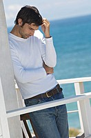 Young thinking man leaning against wall on a terrace, sea in background