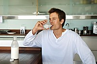 Young man drinking milk in kitchen